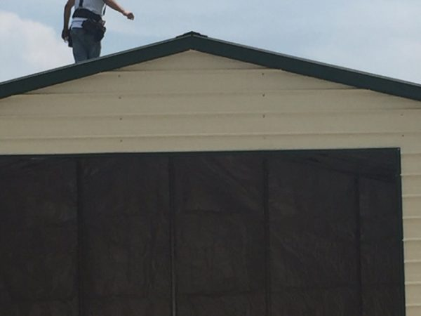 Photo of a crew member standing on top of a commercial garage.