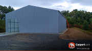 Commercial metal garage building with one roll-up garage door on the side.