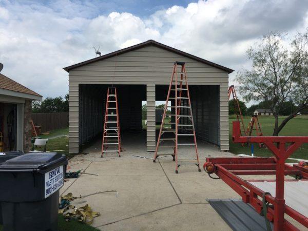 Double wide garage with three garage doors not installed yet.