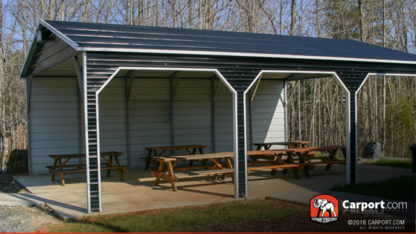 Three bay picnic shelter with one side wall and picnic tables underneath.