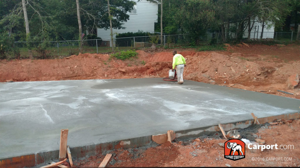 Concrete foundation is smoother out, and a worker carries a bucket across it.