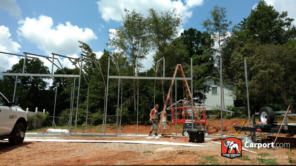 Framing of the building is erected, and two workers use a ladder to assemble the truss system.