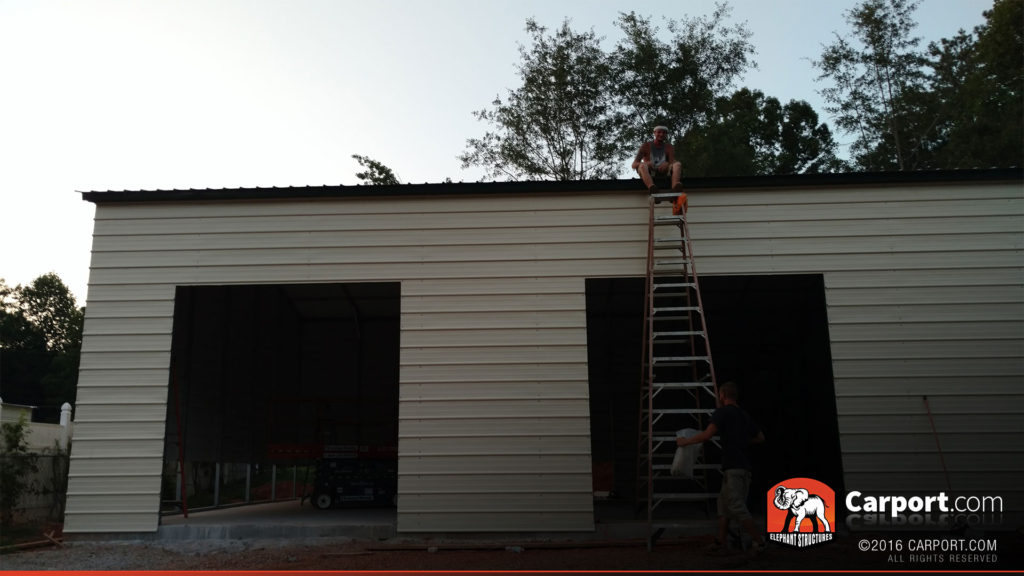 Two roll up garage door openings are visible while the crew climbs a ladder.