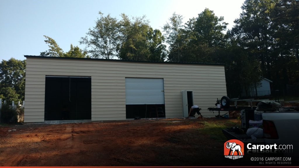 Side view of the garage where two roll-up garage doors are visible.