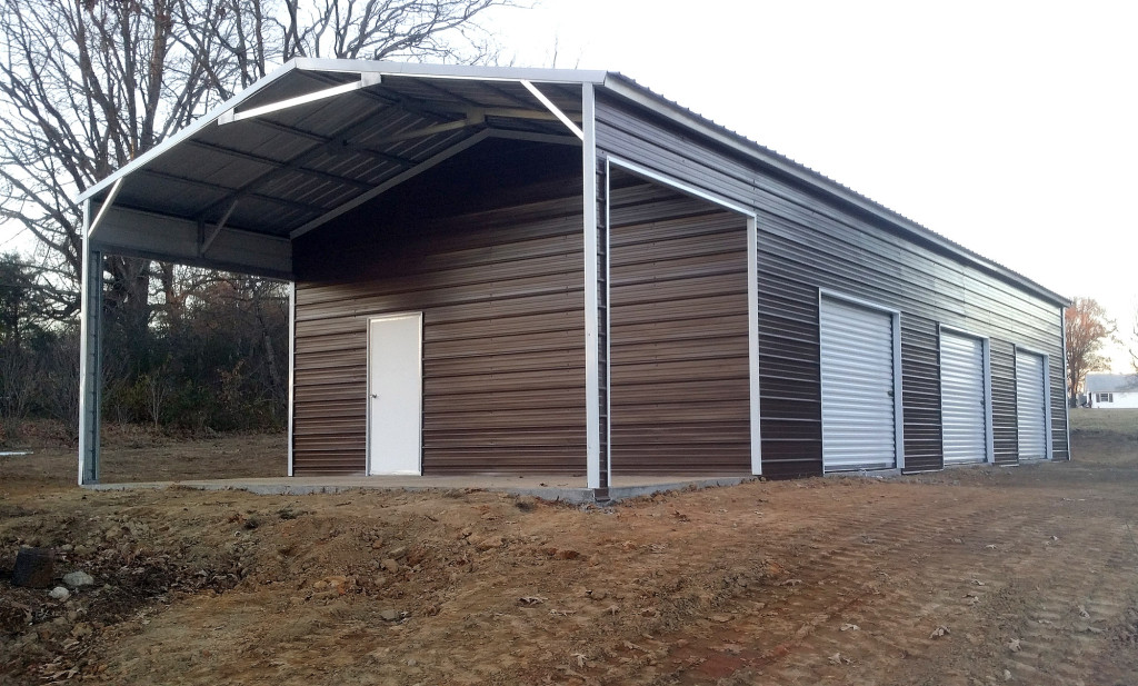 Metal building with three roll up garage doors side installed on a large utility shed, and a porch created out of the left over roofing.