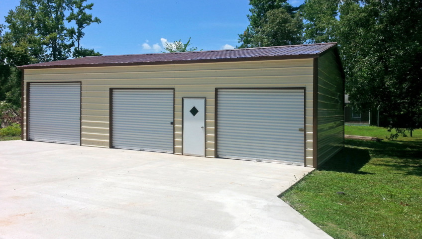 Three metal roll up garage doors with one walk in door on the front.