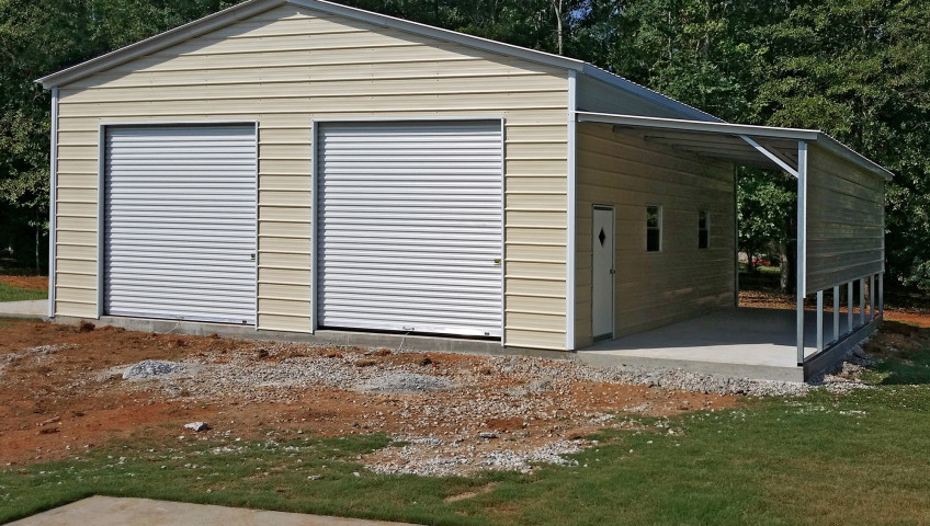Two roll up garage doors on the front of a double wide metal garage with a lean to installed on the side of a concrete foundation.
