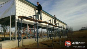 Installers using scaffolding to fasten paneling on to a carport.