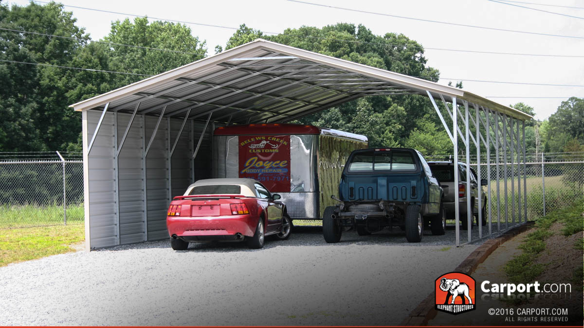 Four car carport with one side enclosed to protect from the elements.