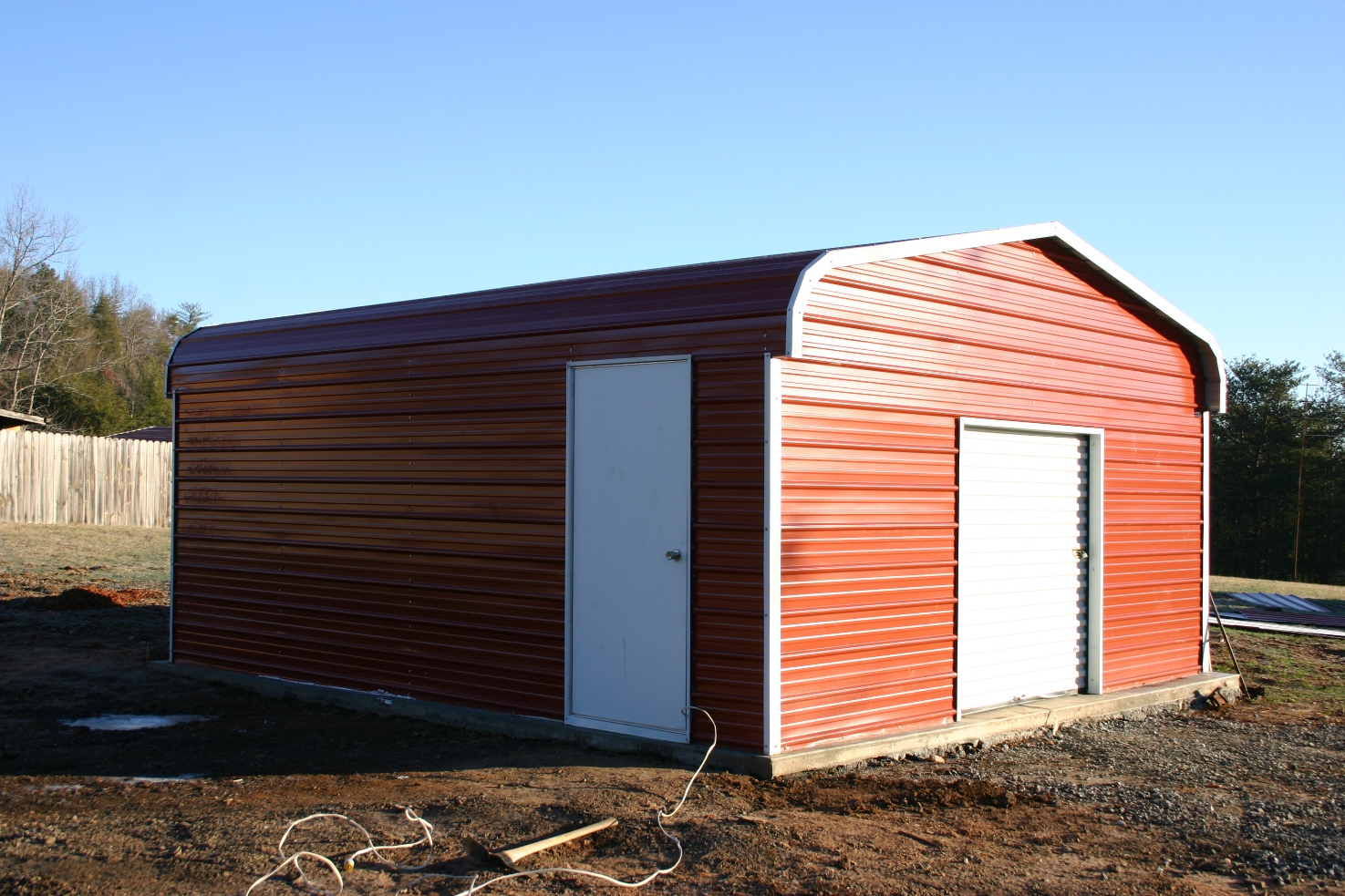 Metal motorcycle garage with red walls and white roll-up garage door.