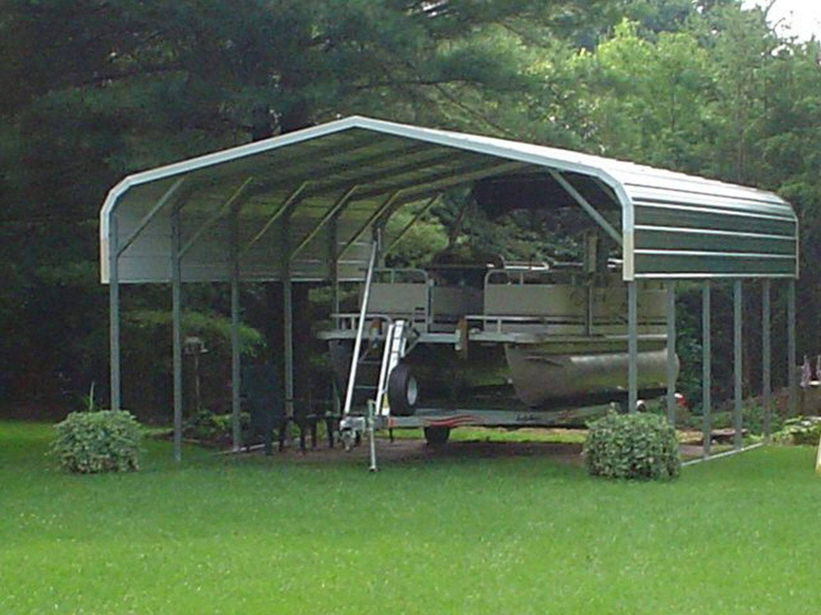 Green pontoon boat cover with pontoon boat parked underneath.