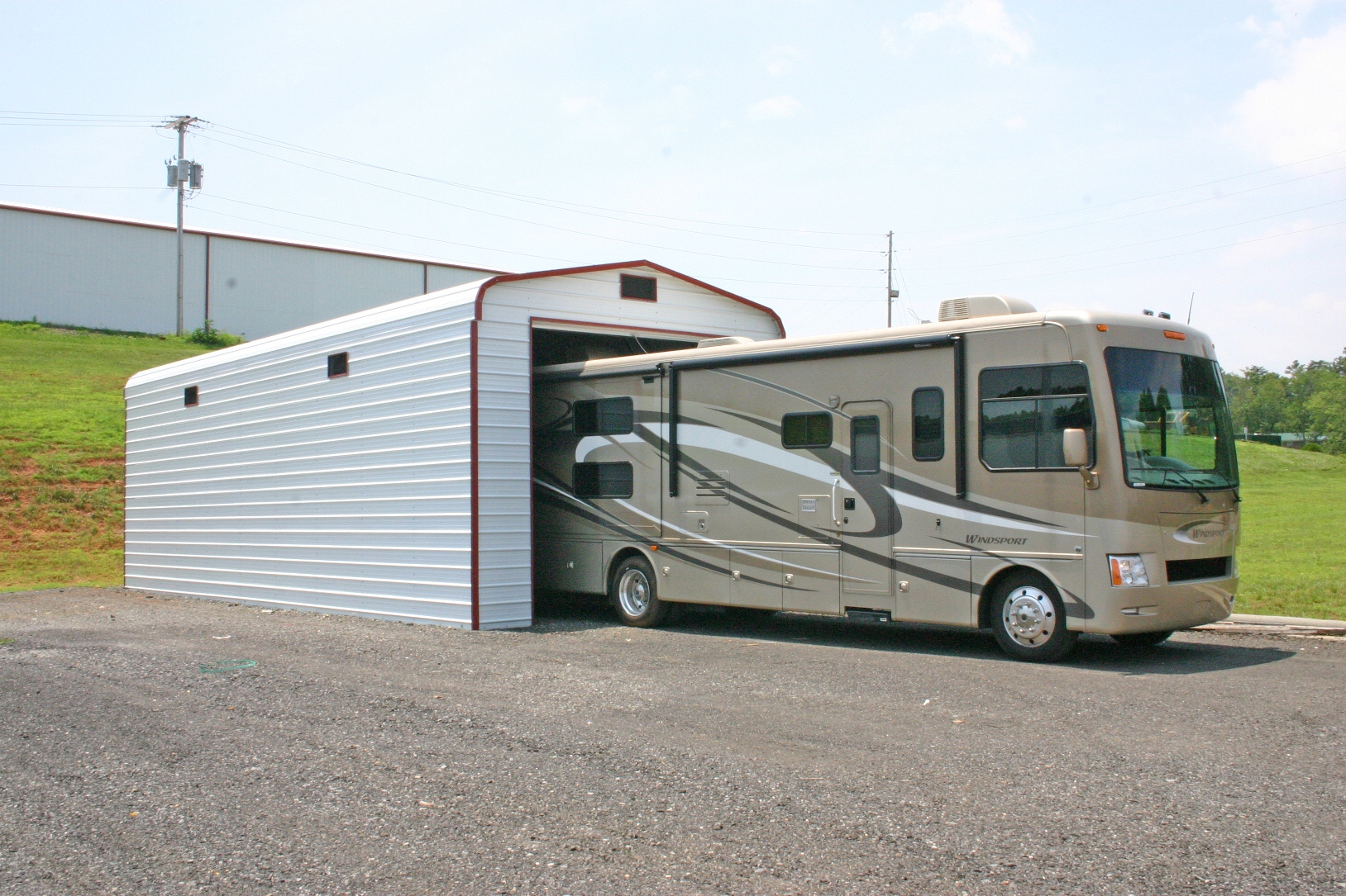 RV metal garage with white sides and ends, and red trim.