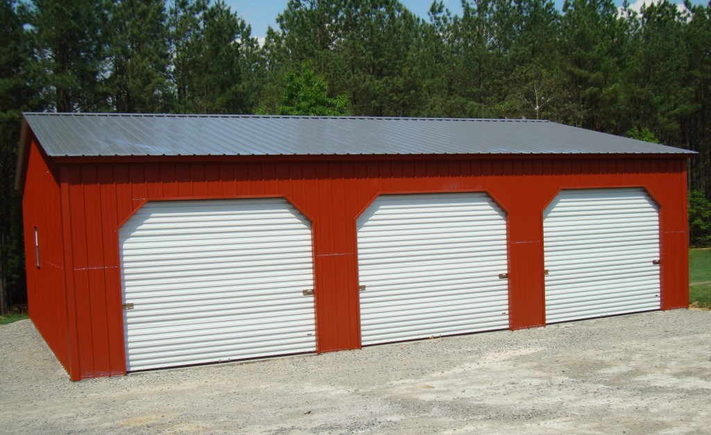 Three car steel garage with 45 degree angle trim, red walls, and galvalume roof.