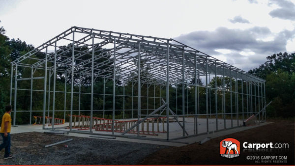 Commercial metal garage building framing on a concrete foundation with ladders laid inside.