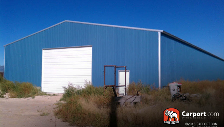 50x100x14 Commercial metal garage building 50 x 100 with blue walls and white trim, one roll up garage door and walk in door.