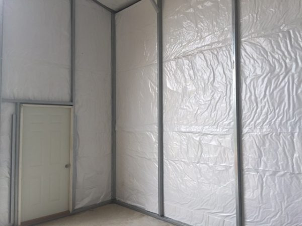 Inside view of commercial metal garage with insulation and man door.