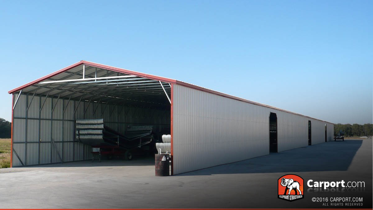 Commercial metal garage with roll up doors and trailors parked inside.