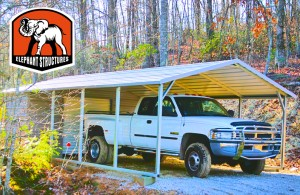 Metal carport used as a truck cover with utility shed and roll up garage door.