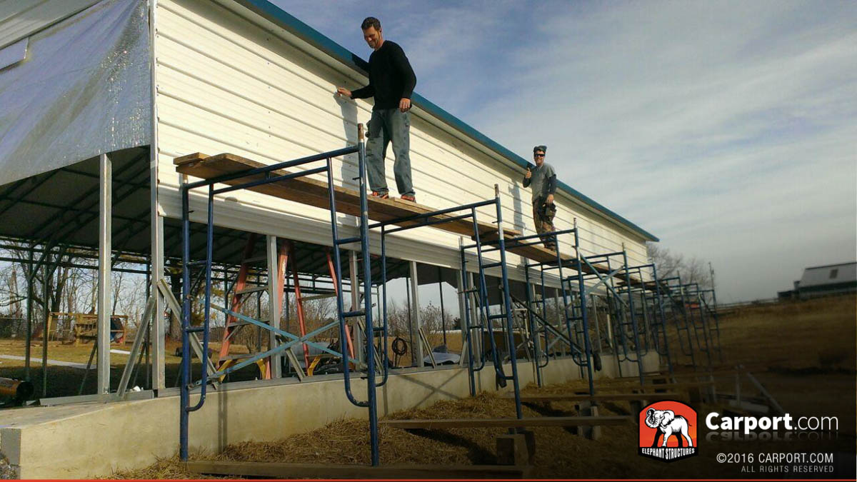 Crew standing on scaffolding with carport during installation.
