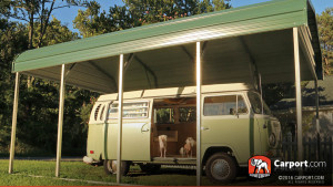A stylish VW Bus parked beneath a green Elephant Structures carport with a regular roof.