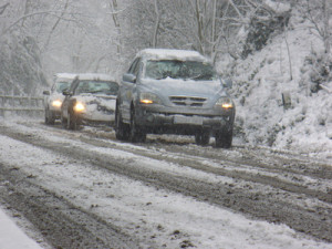 cars traveling slowly down a snow fallen road