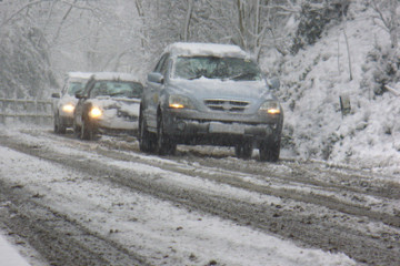 Cars traveling slowly down a snow covered road.