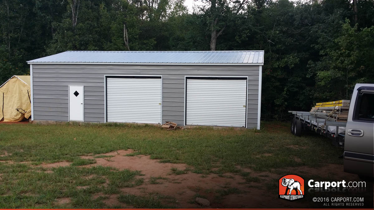 Commercial metal building with two roll up garage doors and one window.