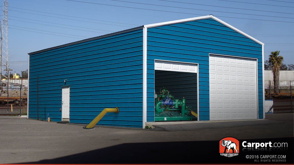 Commercial metal building with two roll up garage doors and water pump inside.