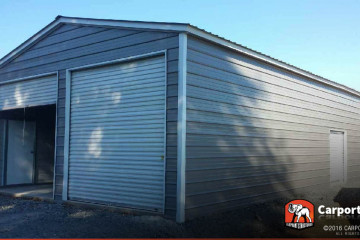 Two car commercial metal building with two roll up doors on the front and one on the side.