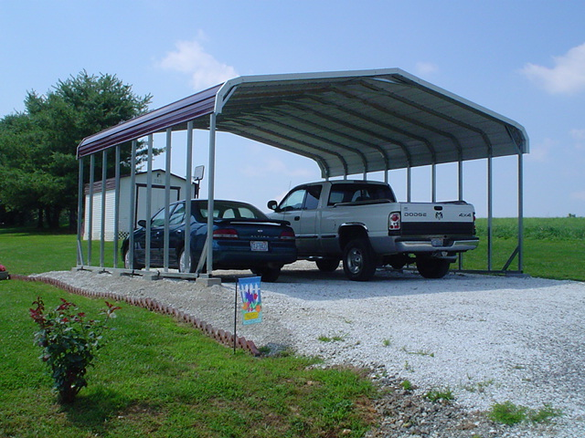 Double carport with red roof and white trim, two cars parked underneath.