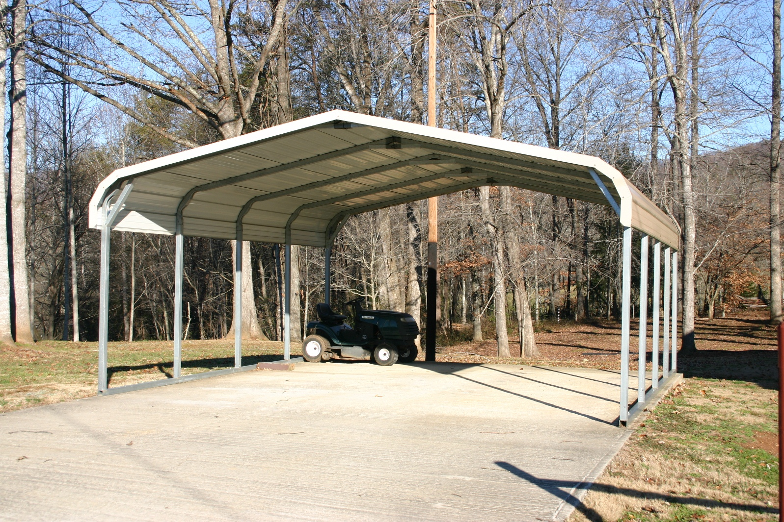 Double wide two car carport with tan roof and white trim.