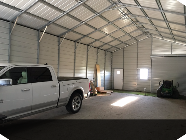 Inside of a double wide garage building with three garage doors, a window, and a single man door with a truck parked inside.