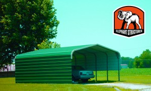 Green carport with half wall on one side and one wall on the other.