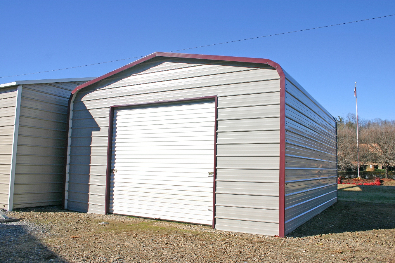 Standard metal garage with white roll up garage door and red trim.