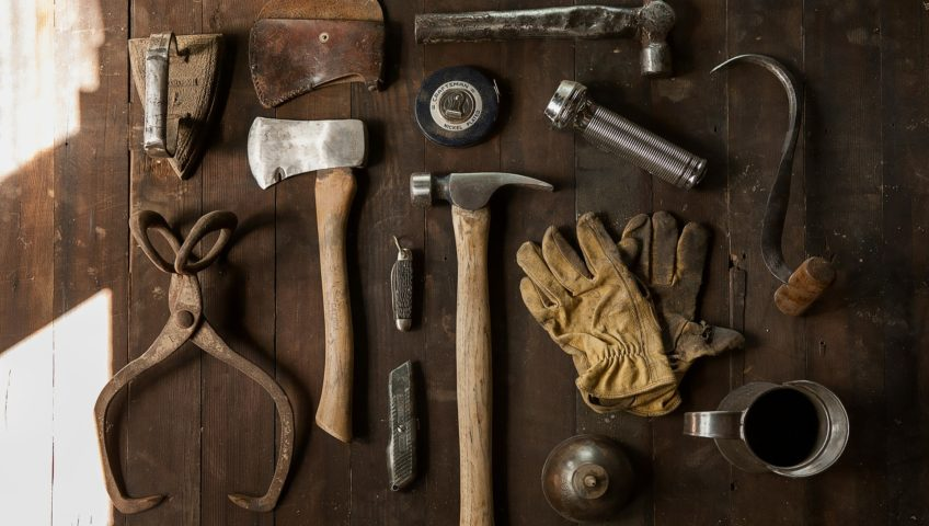 Vintage tools aligned on an old wooden table