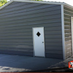 Two car metal garage building with two roll up garage doors and one man door.